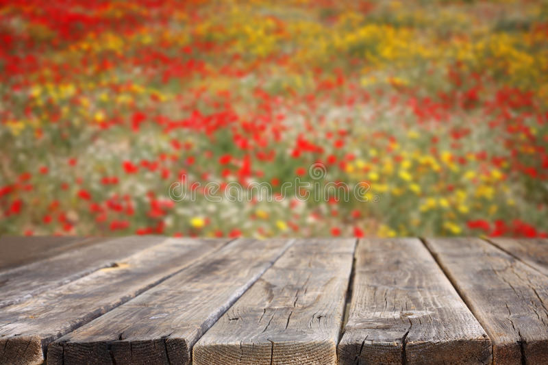 Empty wooden table with field of flowers background. Can be used for product display stock photography