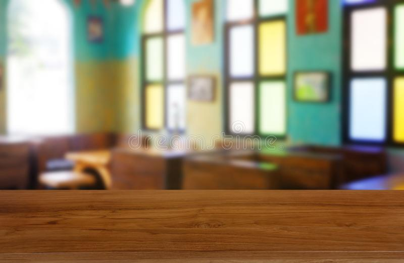 Empty wooden table in front of abstract blurred background of restaurant, cafe and coffee shop interior. stock photography