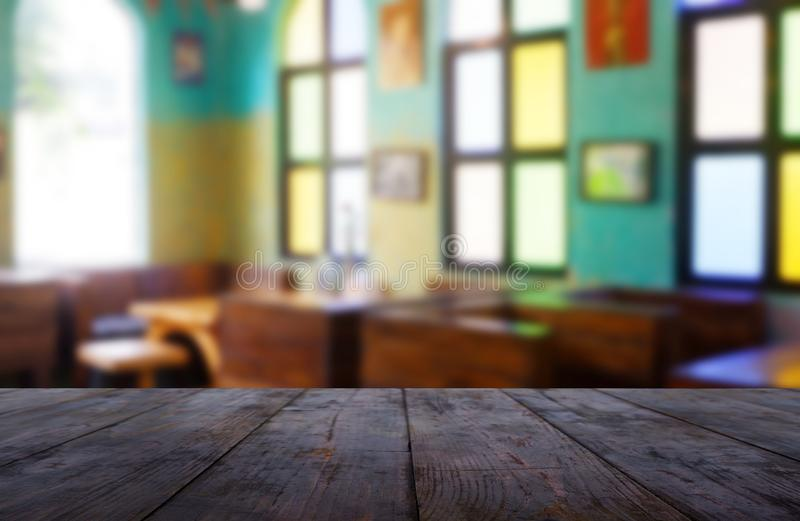 Empty wooden table in front of abstract blurred background of restaurant, cafe and coffee shop interior. royalty free stock image