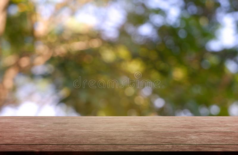 Empty wooden table in front of abstract blurred green of garden and nature light background. For montage product display or design. Key visual layout - Image royalty free stock image