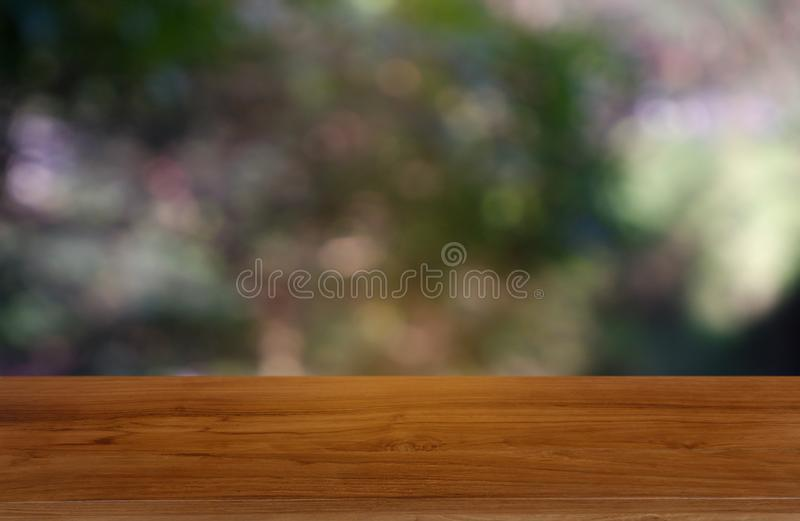 Empty wooden table in front of abstract blurred green of garden and nature light background. For montage product display or design stock photo