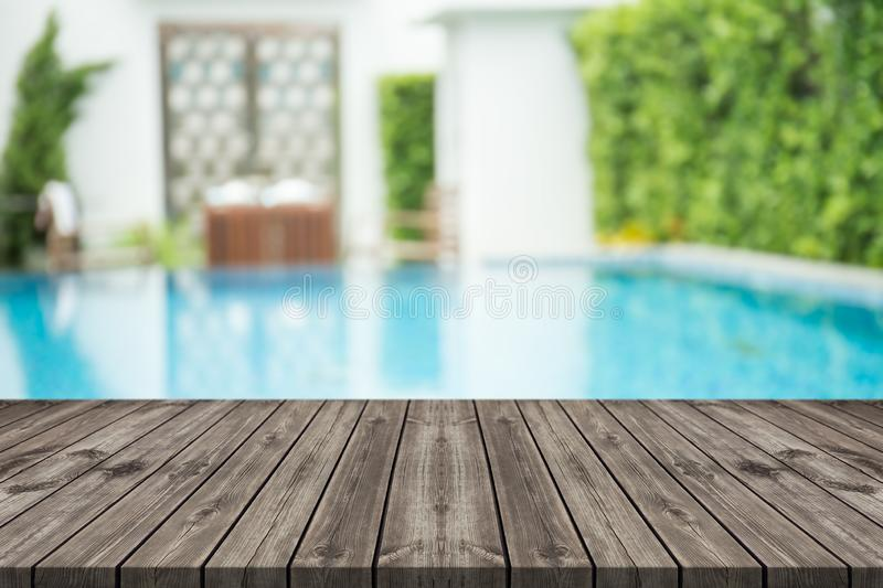Empty wooden table in front with blurred background of swimming pool. At home royalty free stock photography