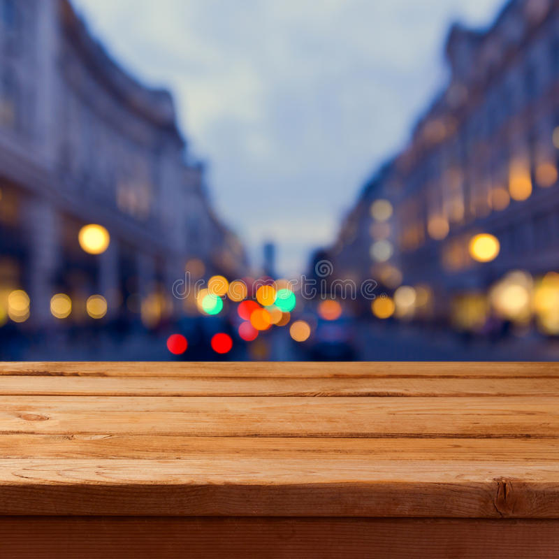 Empty wooden table over city lights bokeh background. Background for product montage display royalty free stock images