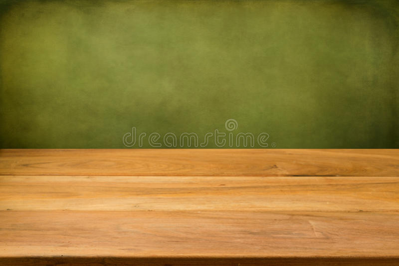 Empty wooden table over grunge green background. stock image