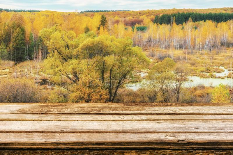 Empty wooden table with picturesque autumn landscape of view from the hill to the lowland with forest and swamps. Mock up for stock photography