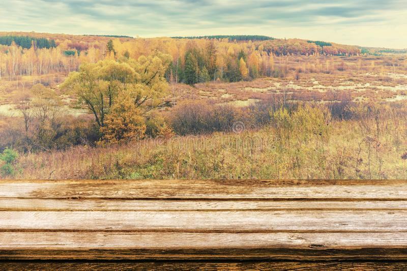 Empty wooden table with picturesque autumn landscape of view from the hill to the lowland with forest and swamps. Mock up for stock images