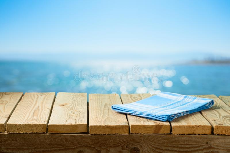 Empty wooden table with tablecloth over sea beach background. Empty wooden  table with tablecloth over sea beach background royalty free stock photos
