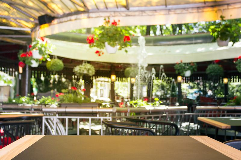 An empty wooden table with a texture, in front of a blurred background. A light street cafe with flowers, plants and a fountain -. Can be used to display or stock images