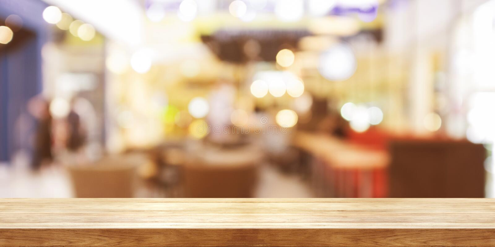 Empty wooden table top with blur coffeeshop window background, P. Anoramic banner. Can be used product display stock image
