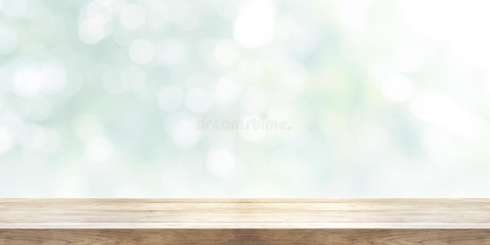 Empty wooden table top with blurred abstract background. Panoramic banner. stock photography