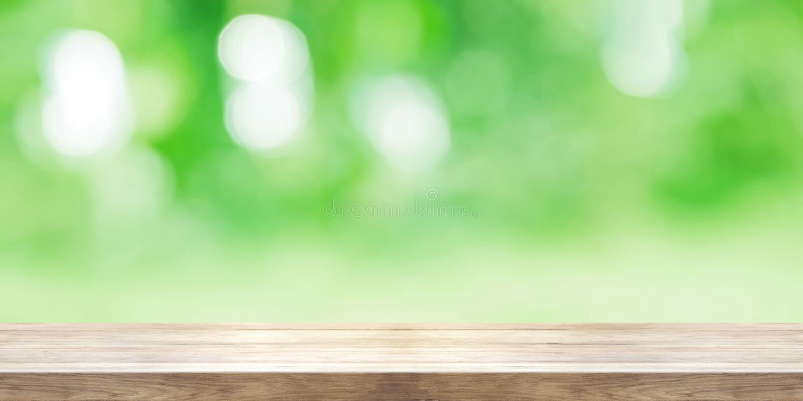 Empty wooden table top with blurred green natural abstract background. Panoramic banner. stock images