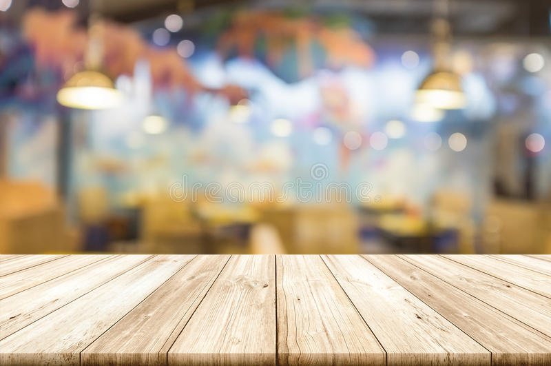Empty wooden table top with blurred restaurant interior background. stock photo