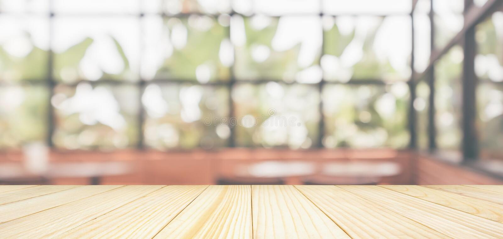 Empty wooden table top with cafe restaurant coffee shop window interior abstract blur defocused with bokeh light royalty free stock image