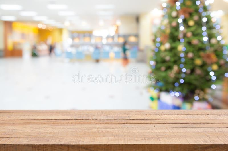 Empty wooden table top over Blurred abstract of decorated Christmas tree with toys, gift box and bauble inside the office building royalty free stock photos