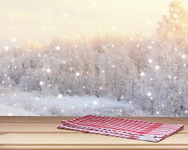 Empty wooden table top with a towel on blurred winter backdrop with snowflakes stock photo