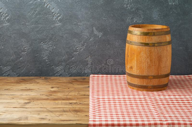 Empty wooden table with wine barrel and tablecloth over black wall background. Empty wooden table with wine barrel and tablecloth over blackboard wall background royalty free stock images