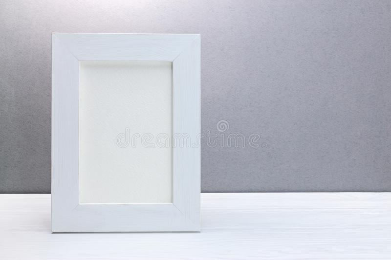 Empty wooden white photo frame against grey wall royalty free stock photos