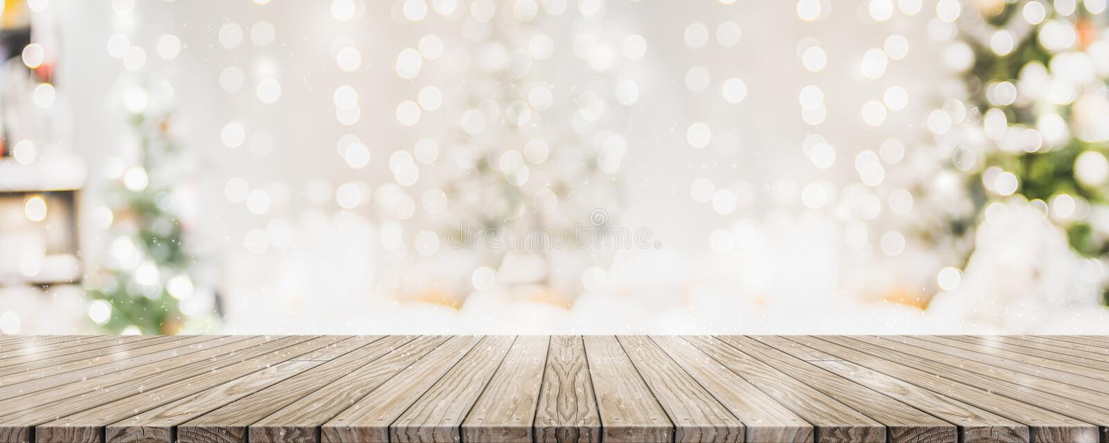 Empty woooden table top with abstract warm living room decor with christmas tree string light blur background with snow,Holiday stock photography