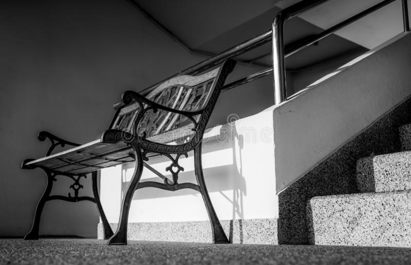 Empty wrought iron bench placed near stairs of the building. Sunshine in to the concrete building. Depressed, sad and lonely royalty free stock photo