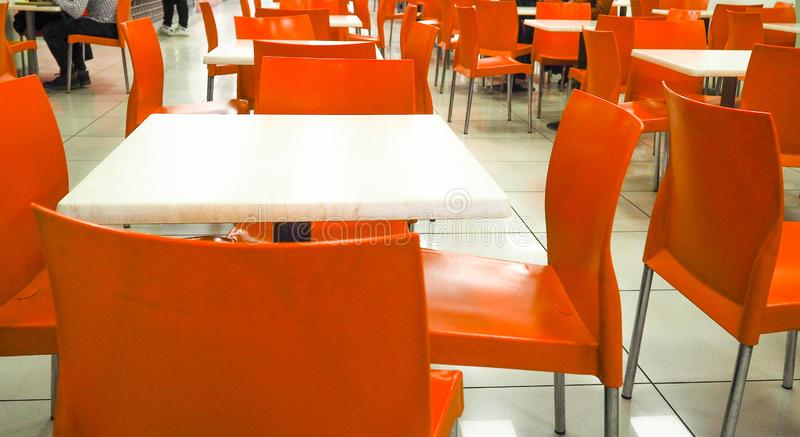 Empty yellow color chairs arranged in the row with the blurred people background in the hall. dining room with orange chairs, stock photo