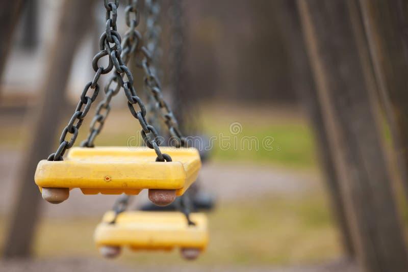 Empty yellow plastic swings royalty free stock photography