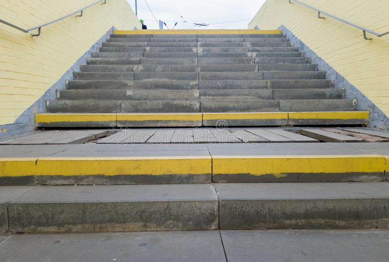 Empty yellow underground pedestrian crossing. Tunnel and daylight at the end. Steps to the top at the pedestrian crossing. A long stock photography