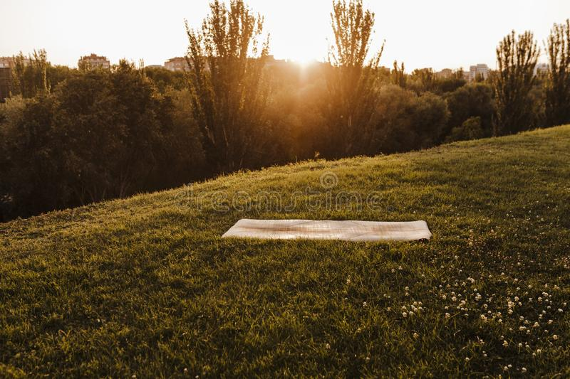 Empty yoga mat at sunset in a park. Ready for yoga exercise concept. Healthy lifestyle royalty free stock photo