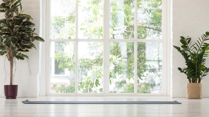 Empty yoga studio interior with windows and unrolled mat stock image