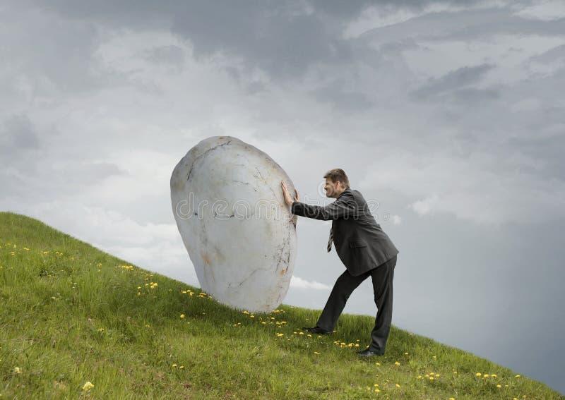 Empujando la roca ascendente foto de archivo libre de regalías