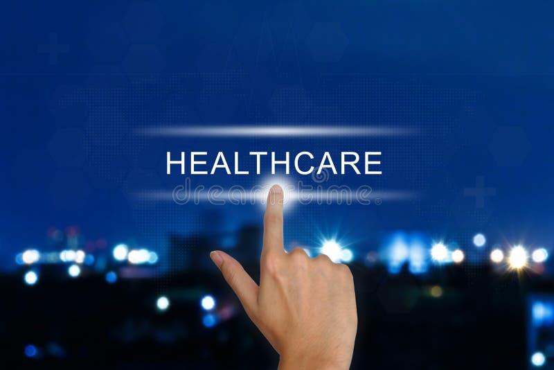 Empujar el botón de la atención sanitaria manualmente en la pantalla táctil foto de archivo