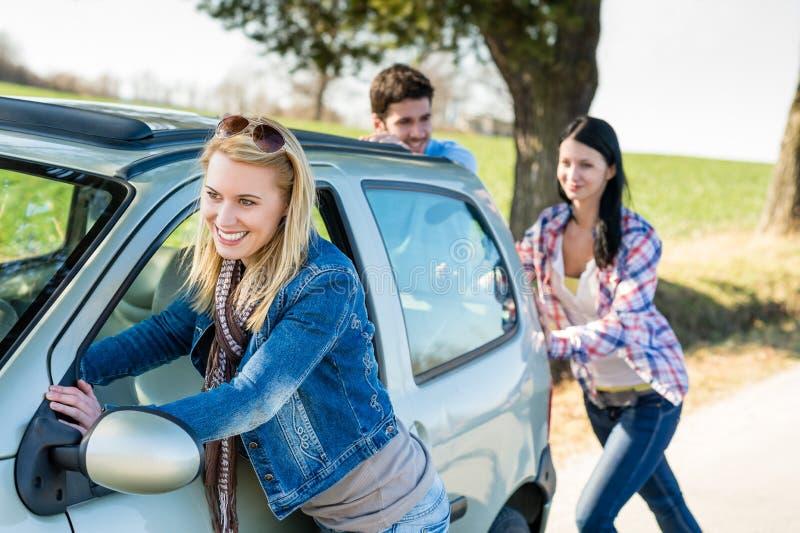 Empujar el camino joven de los amigos del incidente técnico del coche fotografía de archivo
