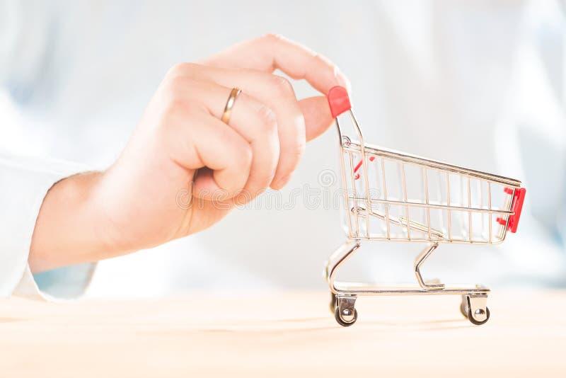 Empujar la carretilla roja del carro de la compra manualmente Concepto de las compras fotografía de archivo libre de regalías