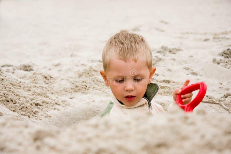 Empuje del muchacho en arena en la playa fotos de archivo