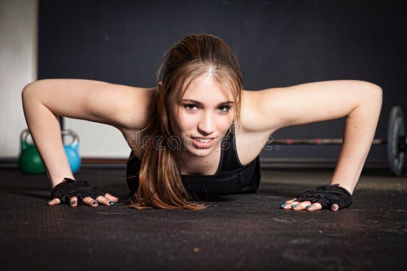 Empuje hacia arriba a la mujer que hace el entrenamiento de la aptitud del crossfit foto de archivo libre de regalías
