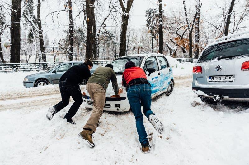 Empurrando o carro na neve, Bucareste, Romênia imagem de stock