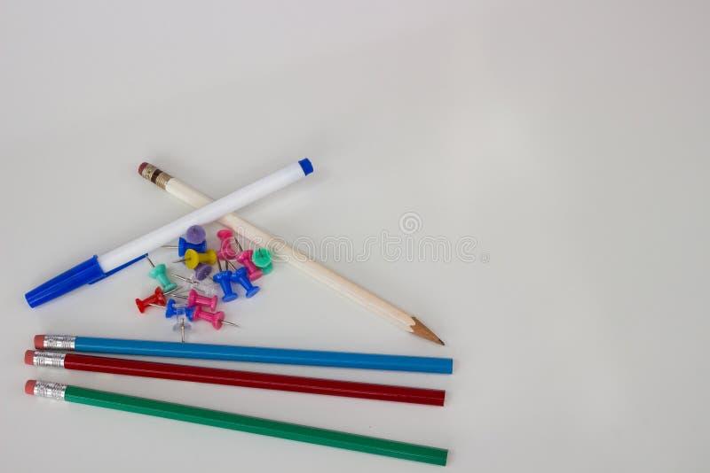 Empurre os pinos, os lápis e uma pena no fundo branco - inferior esquerdo fotografia de stock