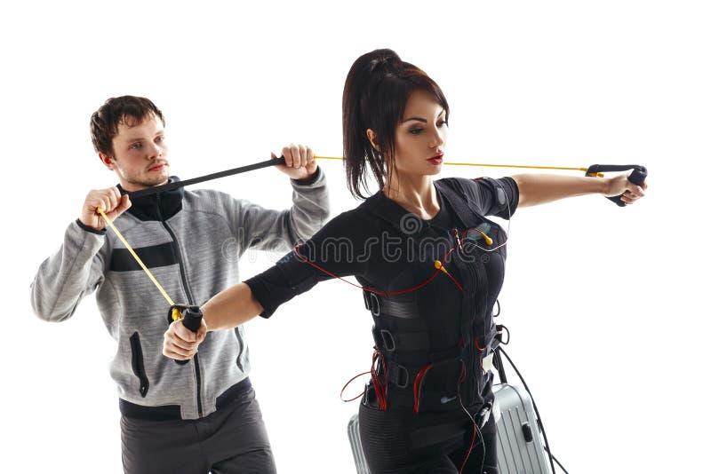EMS健身妇女 胸口与训练缆绳的天桥锻炼与教练 库存图片