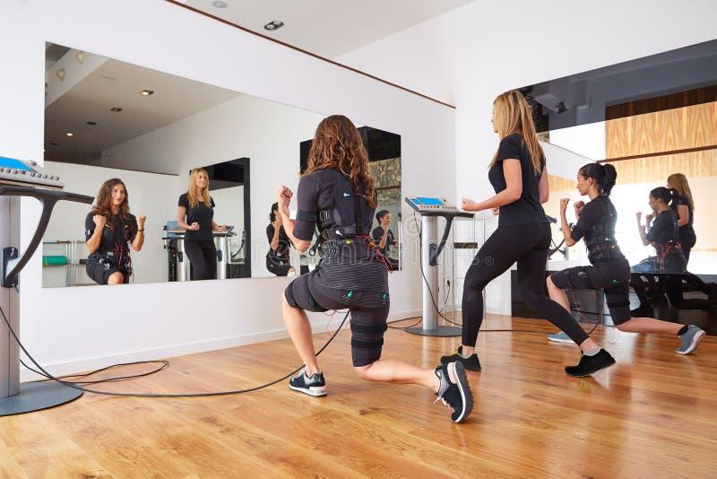EMS electro stimulation women exercises. With trainer coach royalty free stock photo