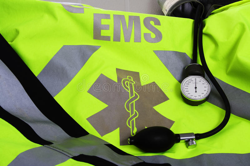 EMS jacket. A yellow and gray EMS jacket and blood pressure cuff royalty free stock photo