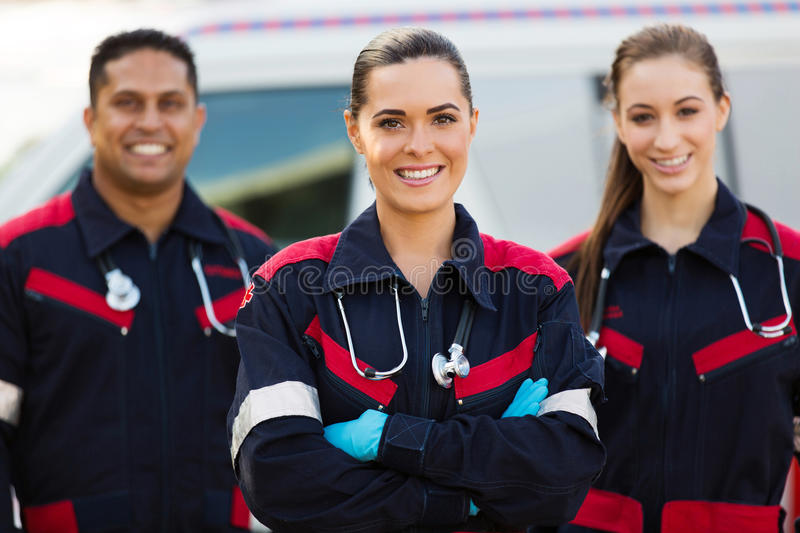 EMT and colleagues. Beautiful young EMT with colleagues in front of ambulance royalty free stock images