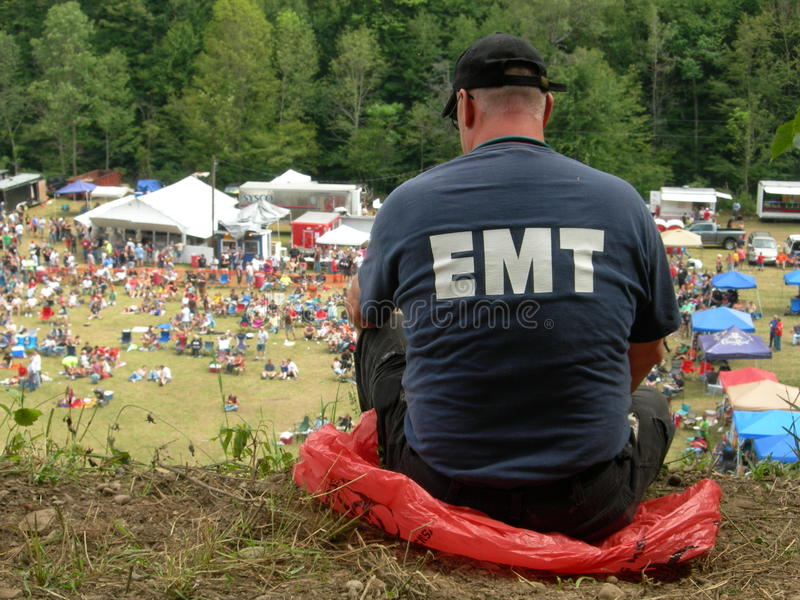 EMT Helping. EMT worker watching the crowd and waiting to help stock photography
