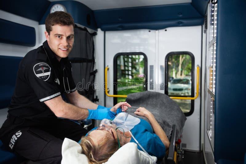 EMT Professional Portrait. Portrait of a male EMT inside ambulance with senior women patient stock photos