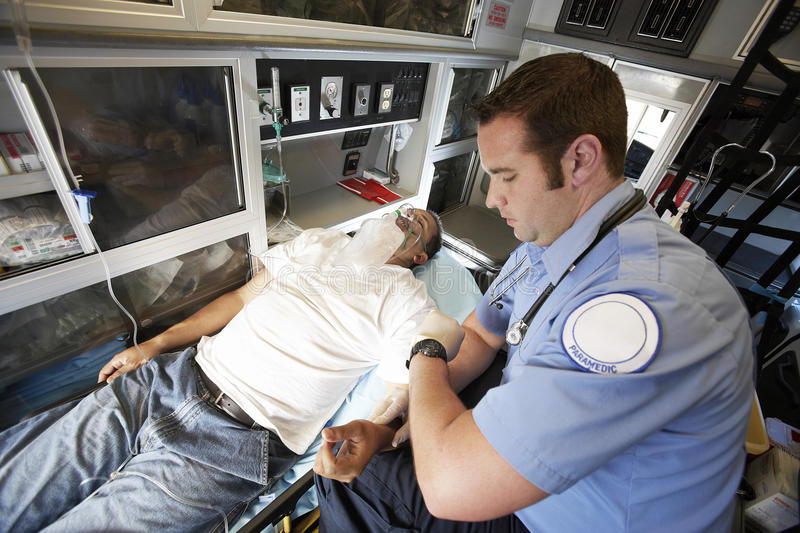 EMT Professional Taking Pulse Of A Man. Male EMT professional taking pulse of a men inside ambulance stock image