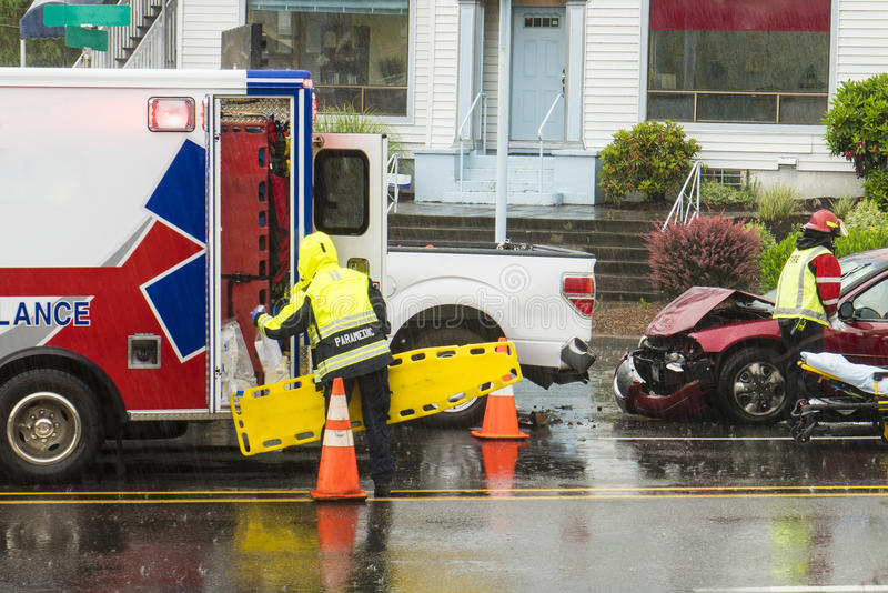 EMT technicians responding to traffic accident. EMT personnel responding to a traffic accident in the rain royalty free stock image