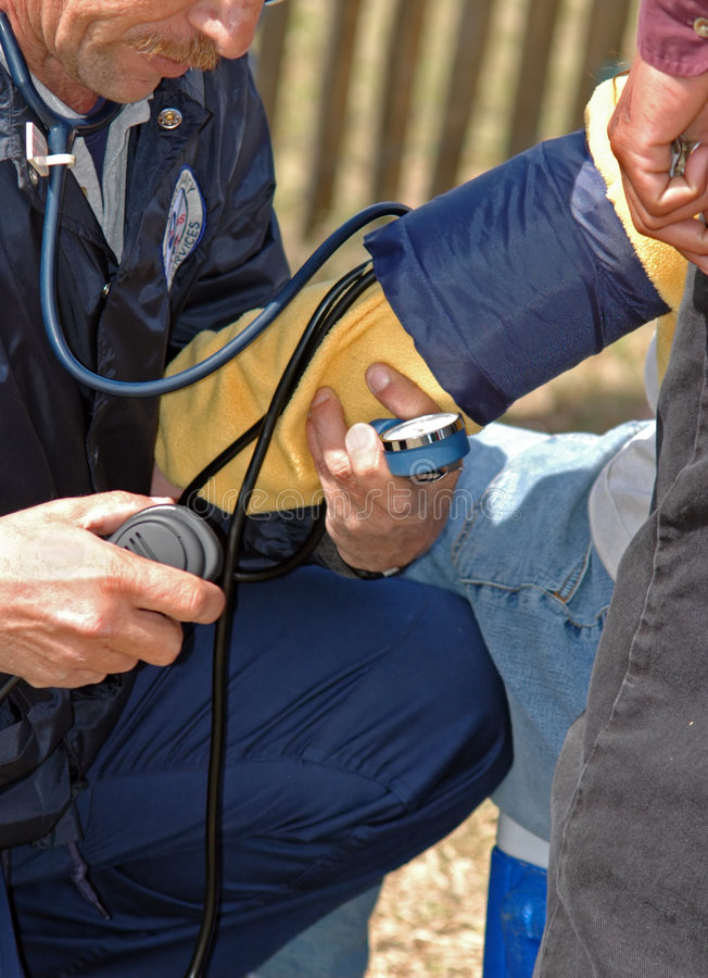EMT treats a patient. Emergency medical technician (EMT) taking a patient's blood pressure in the field stock photography
