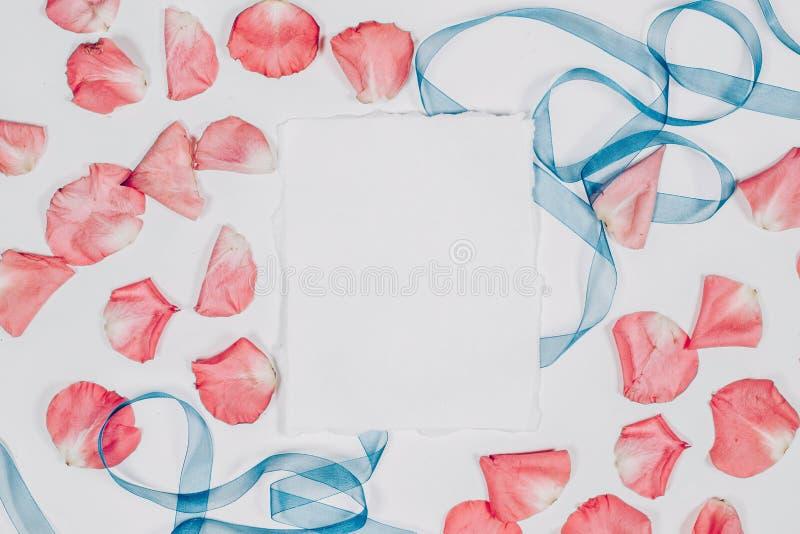 Emty empaquettent la feuille avec les pétales roses et le ruban bleu Configuration plate, vue supérieure, copyspace photos stock