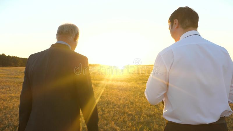 En äldre affärsman i allvarlig dräkt med portföljen i hans hand ger arbetsplan till företagsanställd i afton in arkivbild