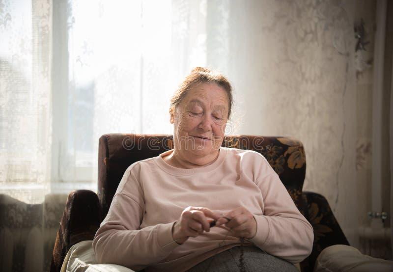 En äldre caucasian kvinna tycker om hennes hobby som sitter i en fåtölj och sticker på bakgrunden av fönstret arkivbild