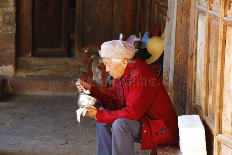 En äldre dam som äter i byn av Shaxi, Yunnan, Kina arkivbilder