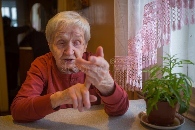 En äldre ensam kvinna talar känslomässigt att sitta på tabellen royaltyfria bilder